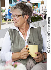 Old woman drinking coffee - Retired pensioner woman sitting...