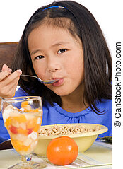 Eating Breakfast - A young Asian Girl eating a healthy...