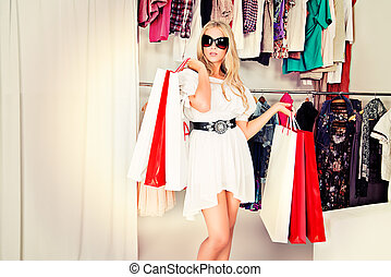 consumerism - Fashionable lady standing with a lot of...