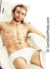weekend in bed - Handsome nude man lying in a bed Isolated...