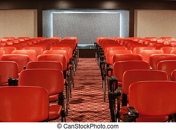 rows of red chairs in empty conference hall - red recliners...