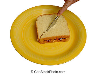 slicing peanut butter and jelly sandwich on a yellow plate -...
