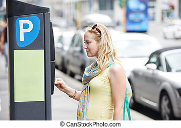 Parking payment - Young female woman paying for parking in...