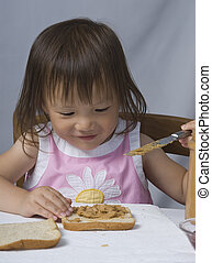 Peanut Butter Sandwich - A young asina girl making a peanut...