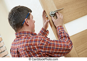 Male carpenter at lock installation - Male worker handyman...