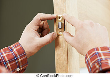 Hand of carpenter at lock installation - Two worker hands of...