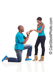African man putting engagement ring on his excited...