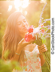 Young Woman with Flowers - Beautiful Young Woman Smelling...