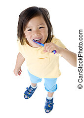 Brushing teeth - A young asian girl brushing her teeth