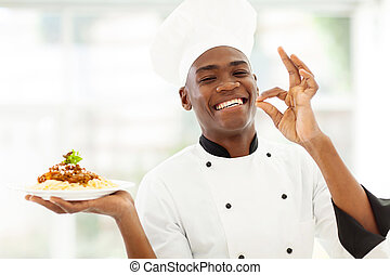 professional African chef holding delicious spaghetti -...