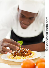 african chef garnishing spaghetti in kitchen