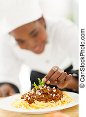 female african cook garnishing spaghetti in modern kitchen