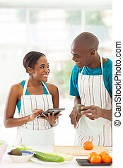 african couple searching for a recipe - smiling african...