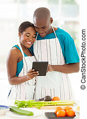 african couple using the internet to look up for a recipe -...