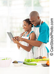 african couple using tablet computer in kitchen - cheerful...