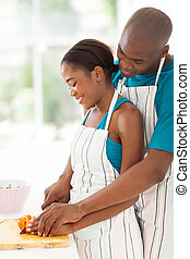 african woman cutting tomato with her husband - smiling...