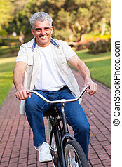 middle aged man riding a bike