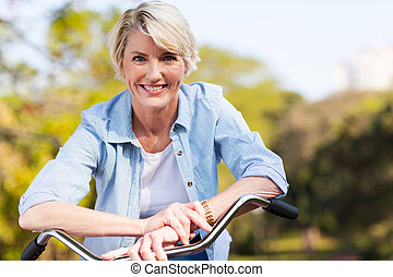 senior woman on a bicycle - close up portrait of senior...