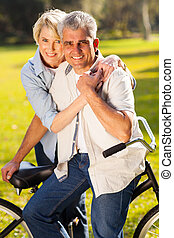 mature couple with a bicycle - beautiful mature couple with...