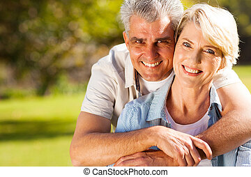 senior man hugging wife - cheerful senior man hugging wife...