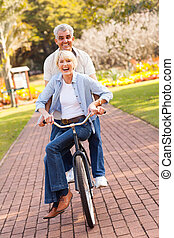 senior couple cycling in a park - cheerful senior couple...