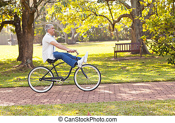 playful senior man riding bicycle