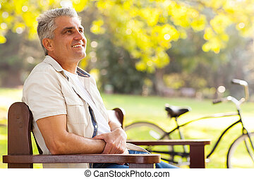 middle aged man sitting at the park - handsome middle aged...