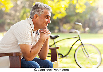 senior man relaxing at the park - happy senior man relaxing...