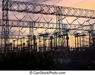 Power lines at sunset - typical power lines, pylon and...
