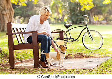 mature woman with pet dog outdoors - happy mature woman with...