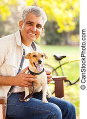mature man pet dog - smiling mature man and pet dog outdoors