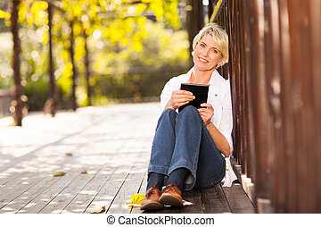 pretty middle aged woman holding tablet computer sitting...