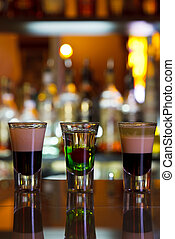 three cocktails layered shots on the background of the bar