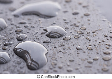 Natural raindrops pattern on wooden table extreme close-up -...