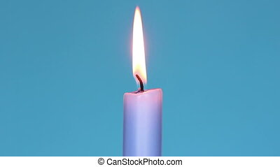 Burning candle with blue background