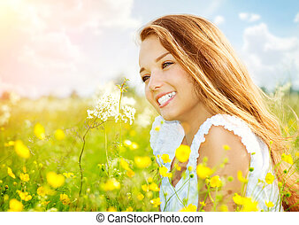 Beauty Girl in the Meadow lying on Green Grass