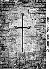 christian crucifix or cross in the stone work of a chapel wall