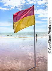 sunny day with flag on beach showing safe to swim