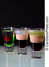 three cocktails layered shots on the dark background