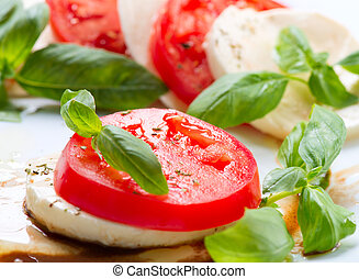 Caprese Salad Tomato and Mozzarella slices with basil leaves...