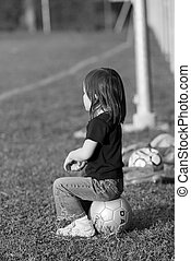Sideline - A small child sitting on a soccer ball on the...