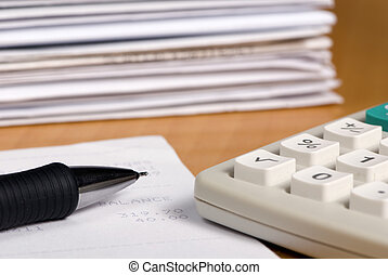 Balance statement - A calculator and pen with piles of...