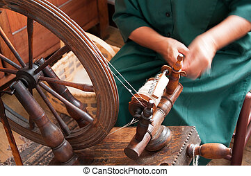 A woman feeds wool into a spinning wheel to make yarn.