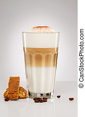 latte macchiato with chocolate powder coffee beans and cookies