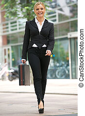 Business woman walking in the city with briefcase - Full...