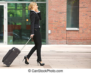Business woman walking with luggage and talking on phone -...
