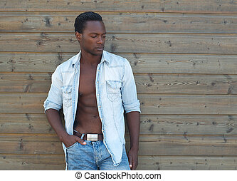 Handsome black man standing outdoors with open shirt