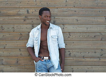 Black man posing outdoors with open shirt