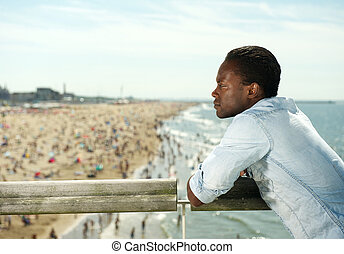Attractive black man relaxing at the beach - Portrait of an...