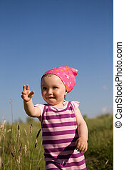 happy baby girl - active baby girl on meadow